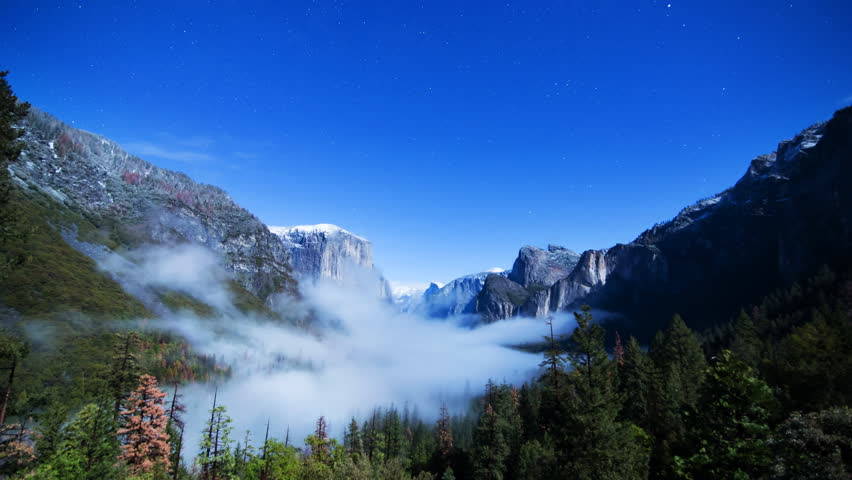 Time lapse of fogs rolling through Tunnel View at full moon night in Yosemite National Park, California