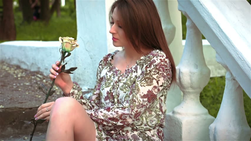 Young woman with metal rose sits on the steps in the Park - HD stock video clip