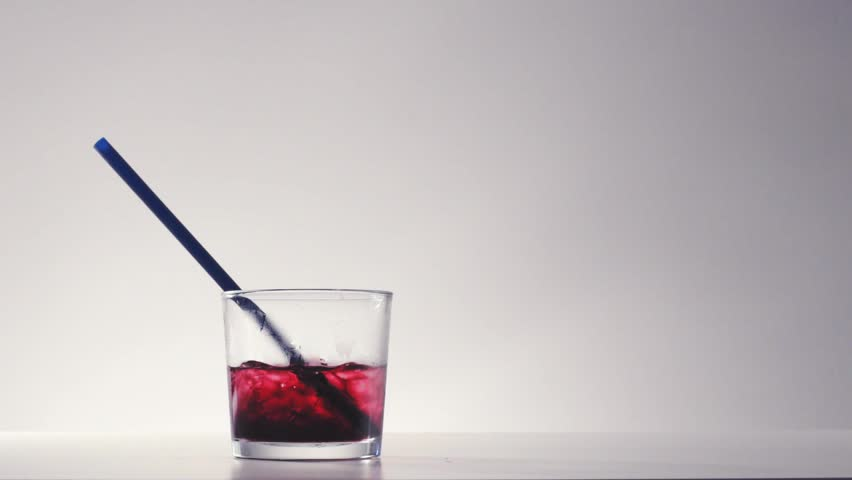 Cocktail glass with crushed ice and red wine or berry beverage inside. Invisible person drinks through straw all Cold refreshment in summer time in slow motion - HD stock footage clip