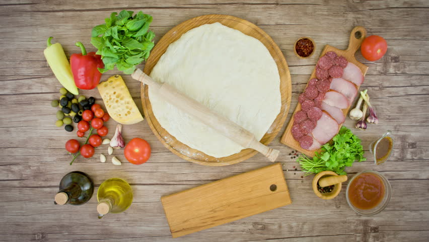 Top view of pizza with ingredients on wooden plate on the table - stop motion animation, 4K