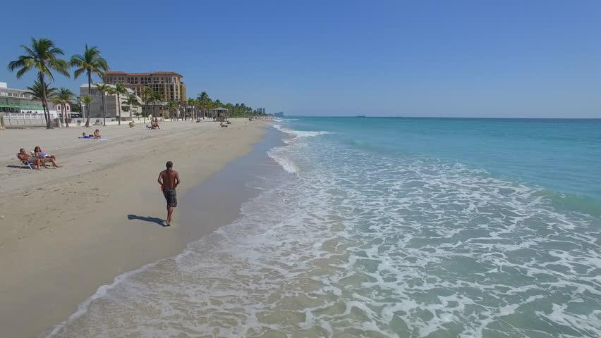 Man running along the coast. Aerial footage of Hollywood beach, Florida, USA - 4K stock video clip