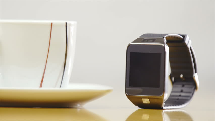 Modern wristwatch and coffee cup closeup 4K. Slide shot of white cup and smartwatch on table. New age communication device. | Shutterstock HD Video #17480173