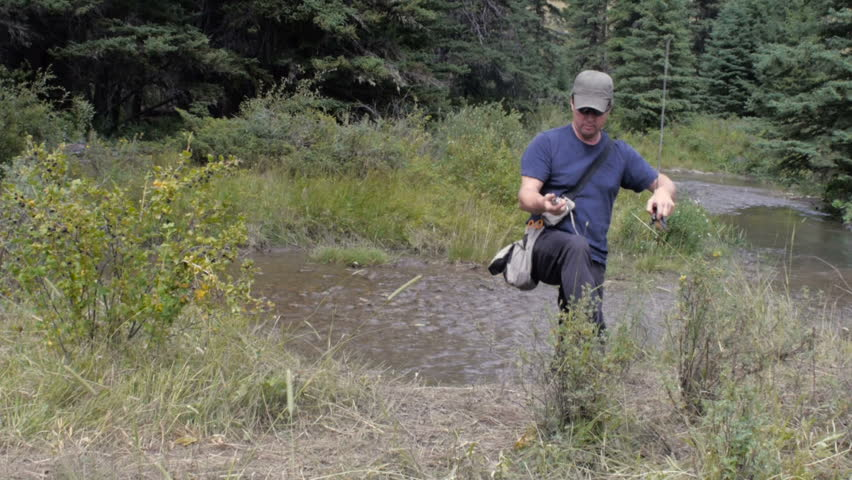 A fisherman shows the camera a freshly caught trout from the mountain stream - HD stock video clip