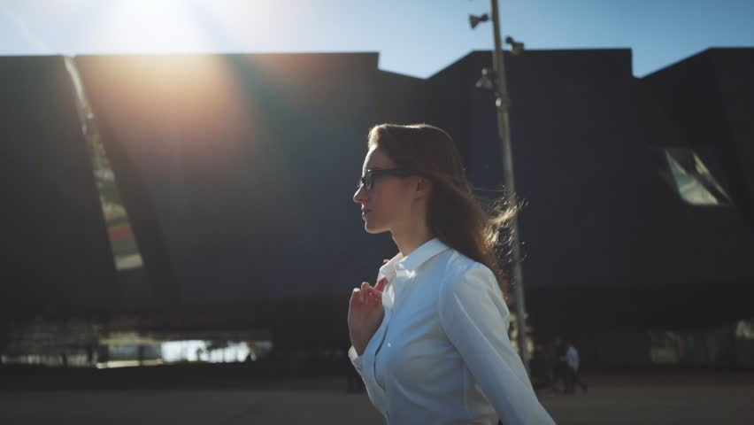 Side view of young successful businesswoman wearing modern suit and walking in the city at break, flare light, sunshine,slow motion