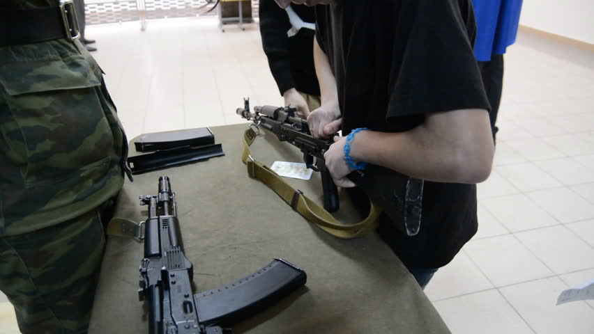 The young man examines a Kalashnikov in the presence of an officer - HD stock video clip