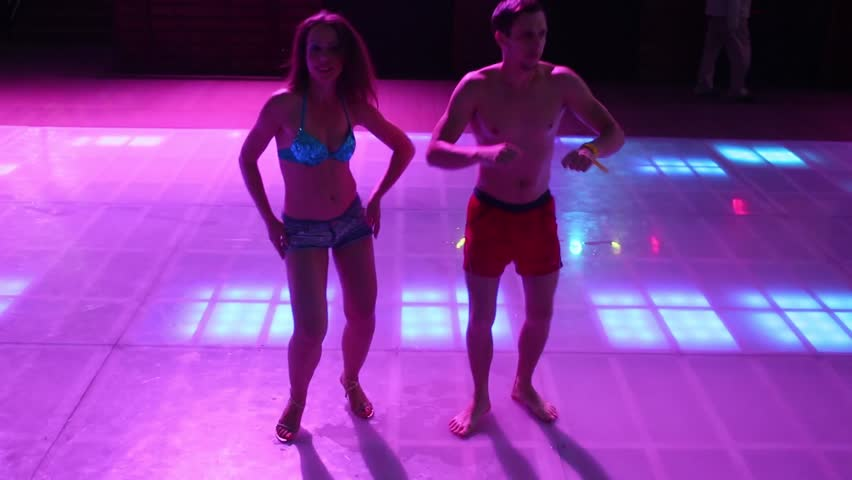 Two of man and woman in shorts are dancing on dancefloor at the evening. - HD stock video clip