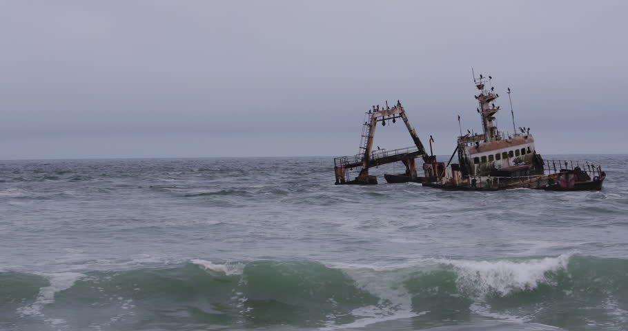 4K view of waves washing over shipwreck on the skeleton coast of Namibia - 4K stock video clip