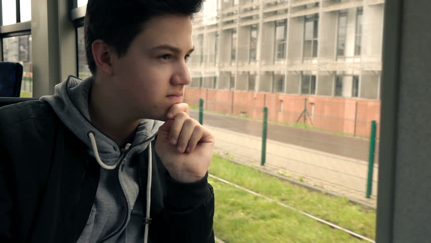 Pensive teenager looking out of window while riding tram, super slow motion 240fps