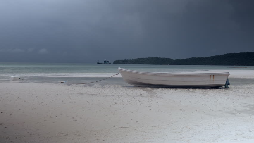 Small boat on a white beach under dark clouds sky  - 4K stock footage clip