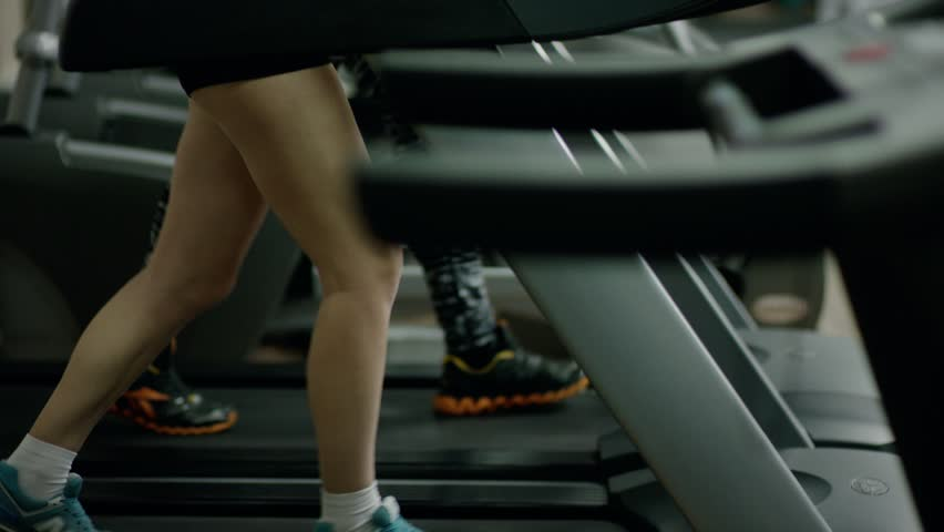 Pretty smiling blond woman walking on treadmill - HD stock video clip