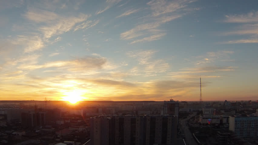 sunset over the city of Yakutsk Russian Republic of Sakha Yakutia in 2016 June. view from the roof of the city under the setting sun taymlaps clouds - HD stock footage clip