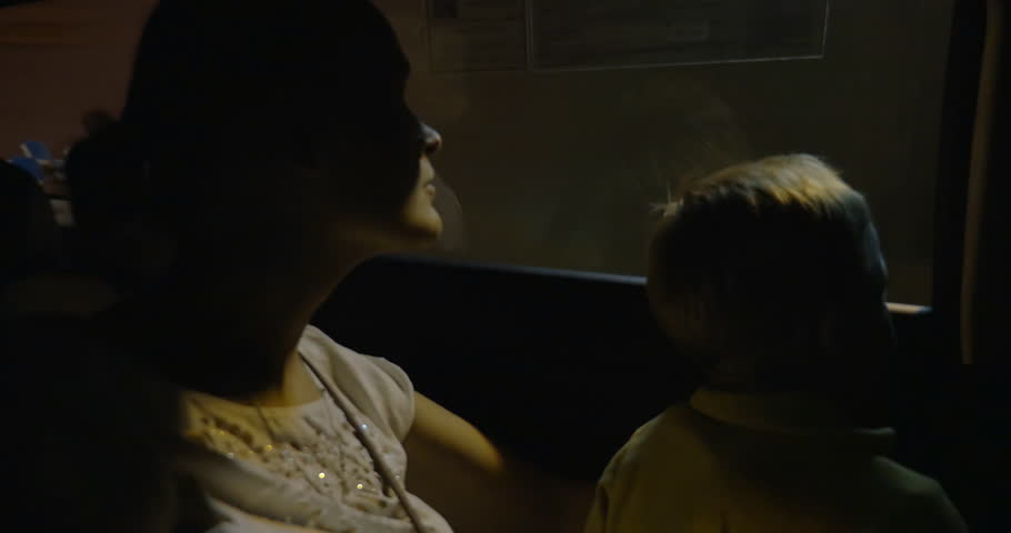 Boy and mother in the car moving through the tunnel. Woman looking out the window and then using a mobile phone - 4K stock video clip