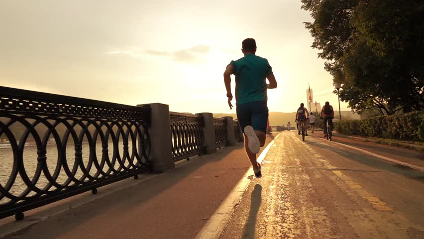 Man in blue running on summer sunset embankment at the camera, Moscow. Super slow motion steadicam shot at 240 fps | Shutterstock HD Video #17773762