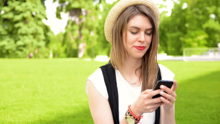 woman with smartphone on green grass with her boyfriend - HD stock video clip
