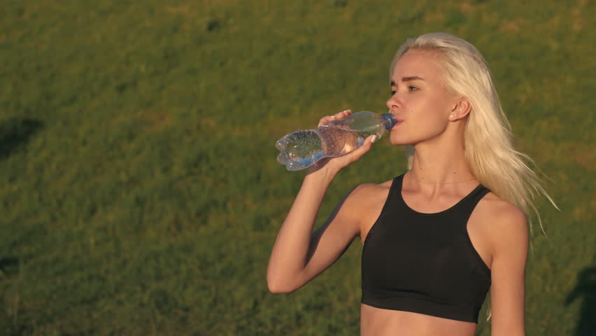 Sporty woman drinking water outdoor on sunny day on sunset | Shutterstock HD Video #17778100