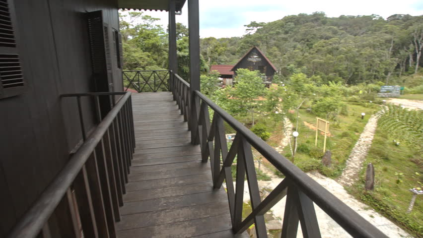 camera moves along wooden balcony of Yersin house on peak of Hon-Ba mountain shows nearby landscape in Vietnam - HD stock video clip