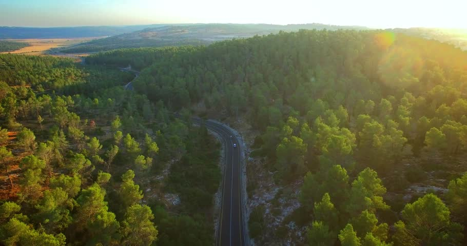 Aerial: Sunset road through the mountains.  Beauty shot