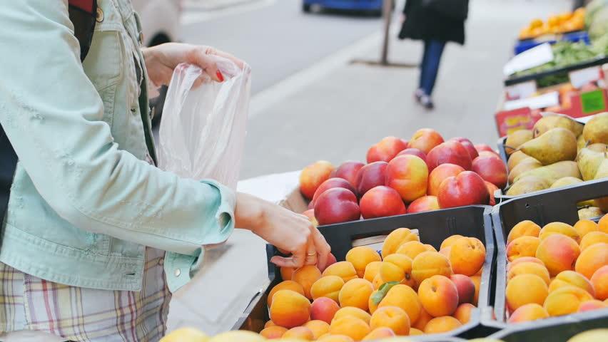 Woman examining fruits at the street market - 4K stock video clip