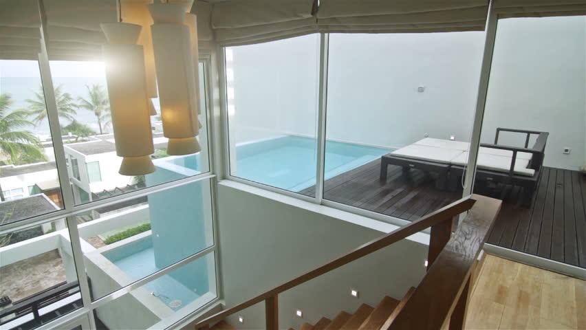 Pan shot of a luxury villa interior. Overlooking the outdoor tropical scene.