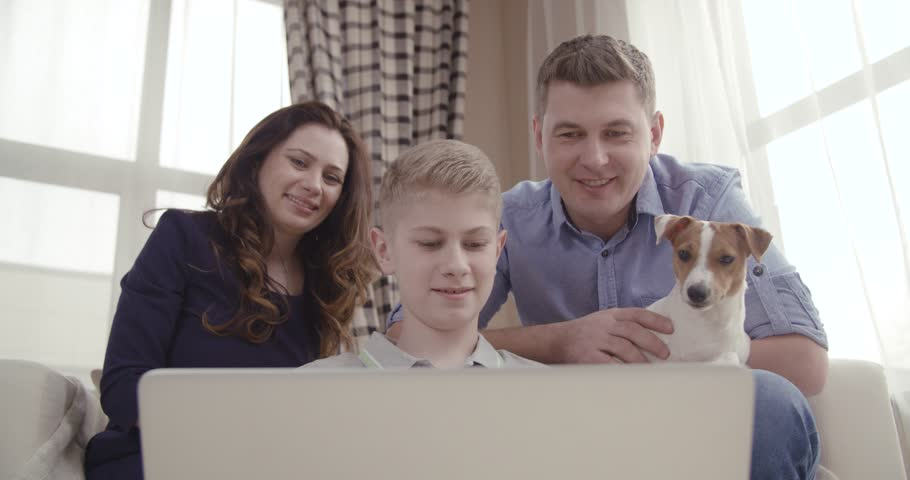 Happy family with cute dog talking to relatives using video chat on laptop at home 4K - 4K stock video clip