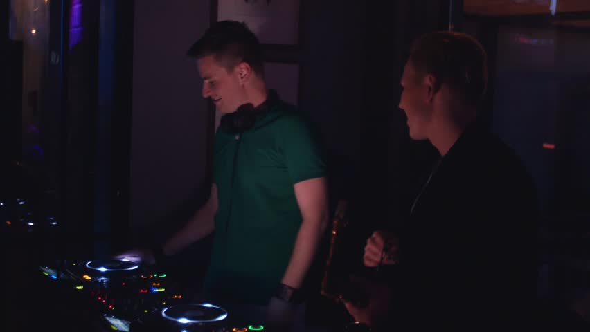 Duet of Dj and man with saxophone perform on party in nightclub. Musicians. Holidays - 4K stock footage clip