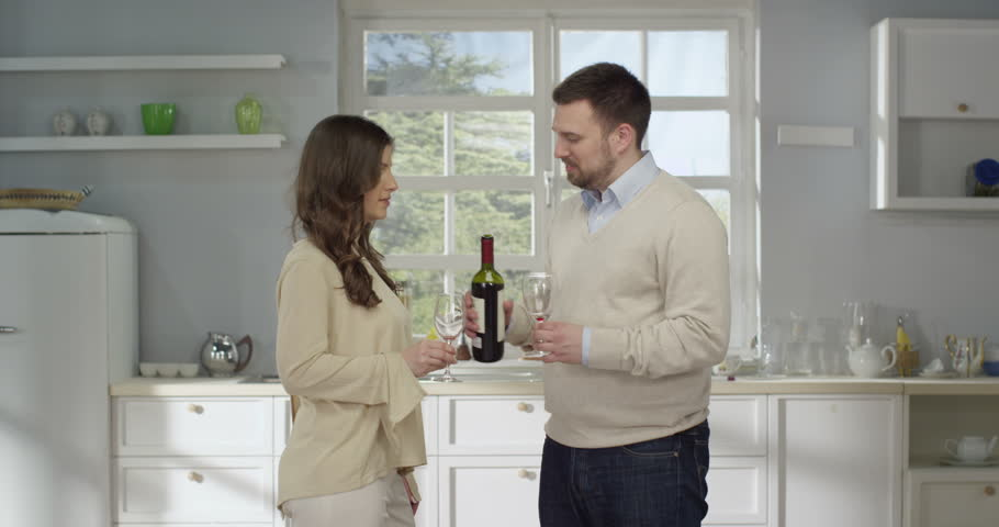 Smiling adult couple toasting with wine in the kitchen.   | Shutterstock HD Video #17927113