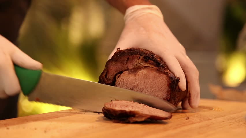 Chief slicing roasted piece of meat. Steak.