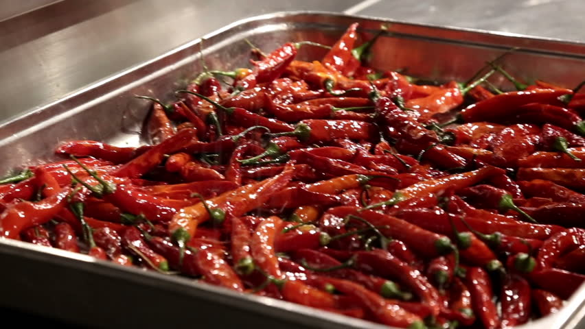 Red peppers get salt on a plate.