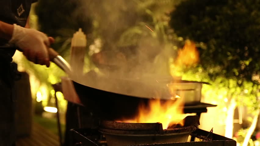 Professional stir fry in slow motion. Stir fry on gas, flame.