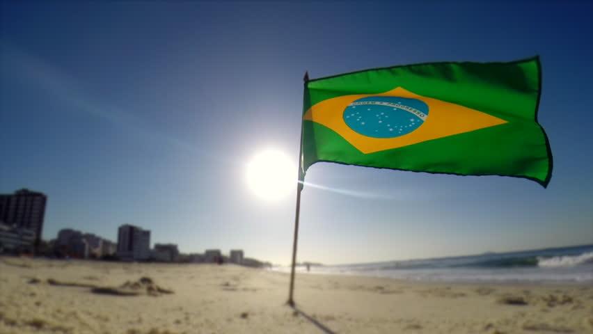 Brazilian flag blowing in the wind in morning sun on Ipanema Beach in Rio de Janeiro, Brazil - HD stock video clip