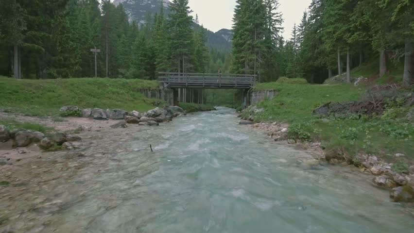 Drone aerial flying over a wild mountain river with woman on the bridge in Dolomites, Italy Alps - 4K stock footage clip