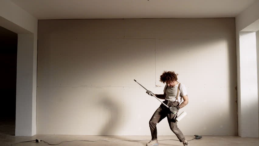 Funny curly man wears pants with suspenders acts like he is playing rock electronic guitar instead of brush roller