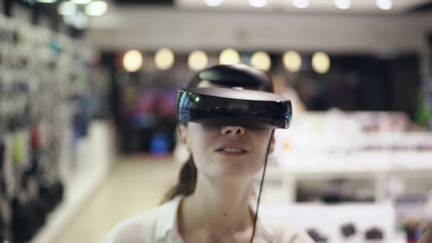 Young woman getting experience in using vr-headset in a mall. Close up