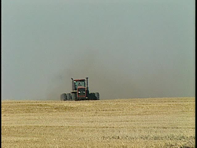 head on tractor tilling long lens (BetaSP) - SD stock footage clip