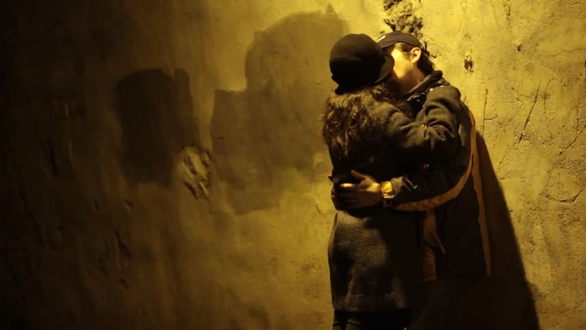 Young couple in love kissing. The boy sits leaning on ancient wall of a fortress, and the girl in his arms.  - HD stock video clip