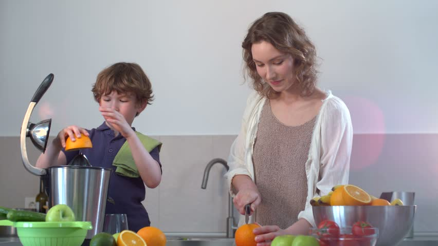 Young Caucasian Mother and Child Homemade Fresh Orange Juice in Kitchen with Electric Juicer