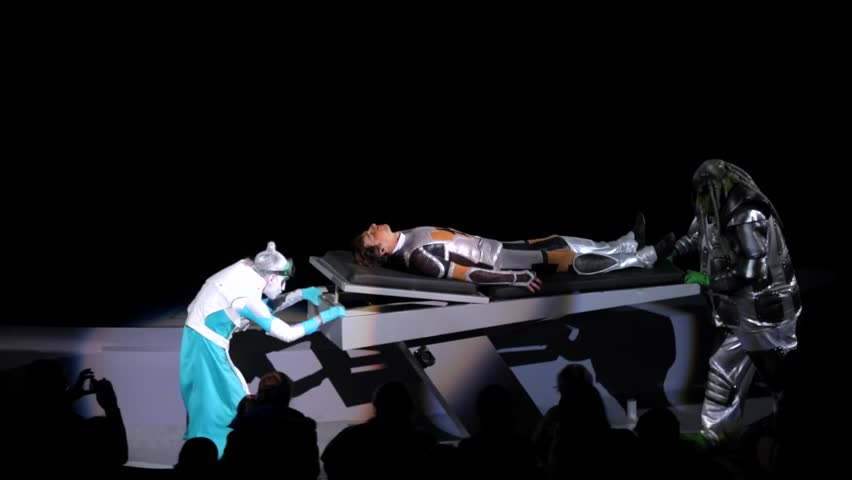 """ST. PETERSBURG, RUSSIA - JANUARY 2, 2016: Brothers Zapashny circus, """"UFO. Alien Planet Circus"""" show in Saint Petersburg. Two aliens roll a human on the stretcher along the spectators seats"""