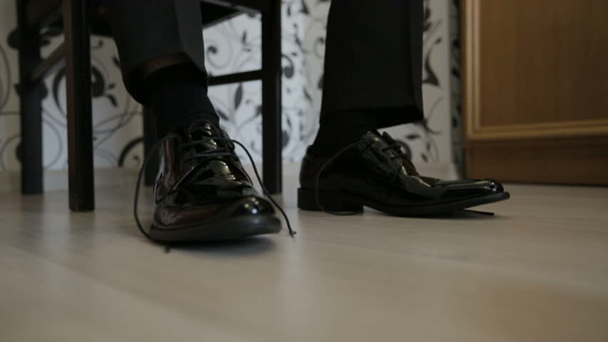 Man tying shoe laces on the floor. Close-up. - HD stock footage clip