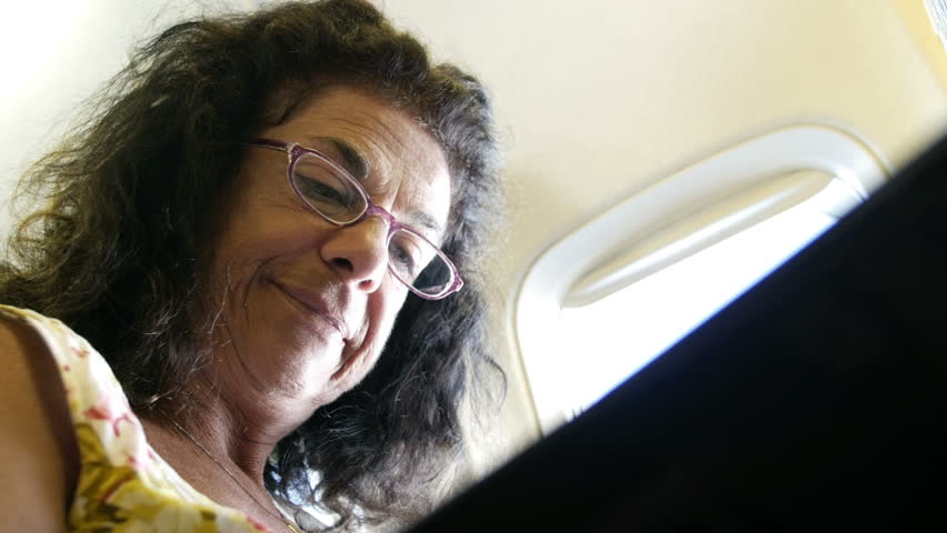 Mature woman reading magazine on the airplane and smiling. | Shutterstock HD Video #18168448