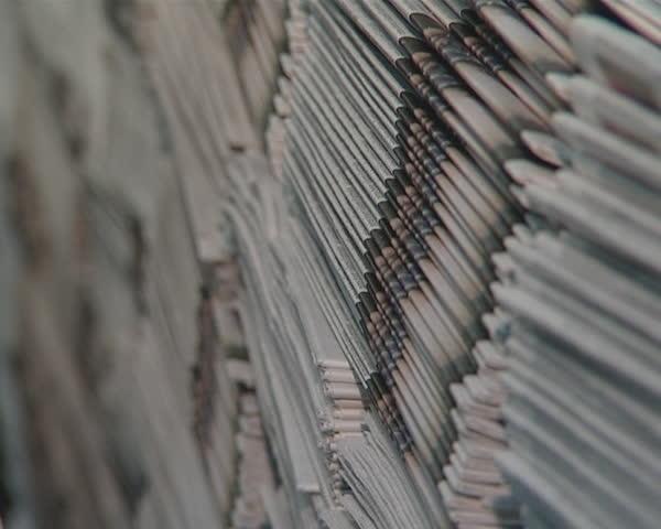 Huge piles of printed newspapers printing shop.