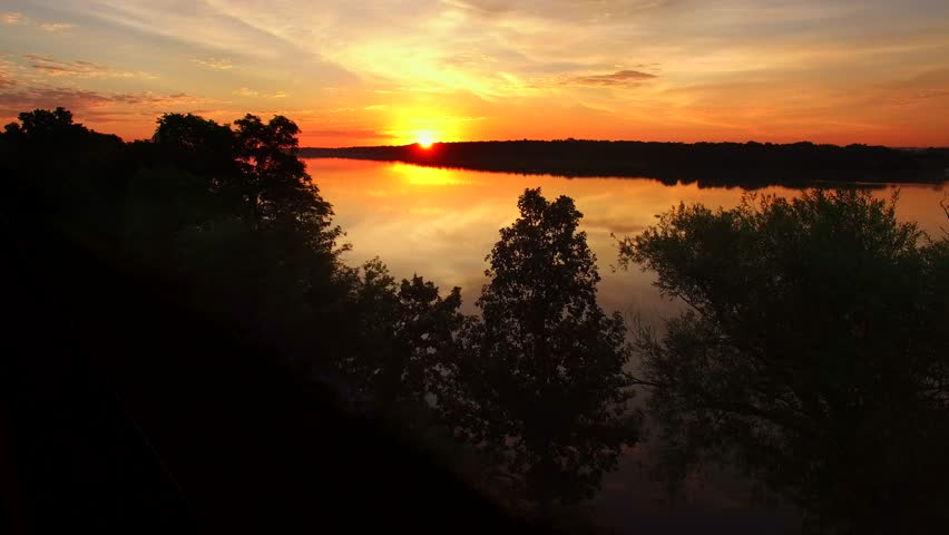 Moving aerial view of spectacular colorful sunrise over smooth river waters.
