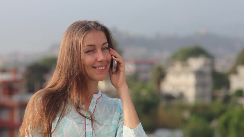 Beautiful Young Professional Woman Has a Telephone Conversation on the Roof of the Office Balcony in the City During the Day. She Stands up to His Waist, Smiling and Hair Developing on a Wind.