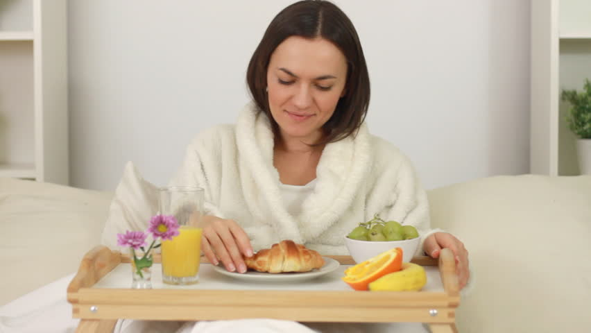 Woman eating breakfast in bed stock footage video 1825136 for How to buy a bed and breakfast