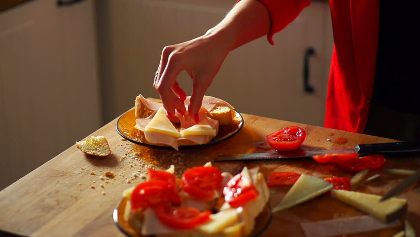 Woman preparing sandwich, putting cheese on bread in kitchen, super slow motion 120fps