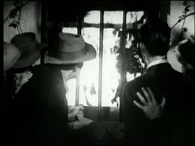 People watching blazing fire through window