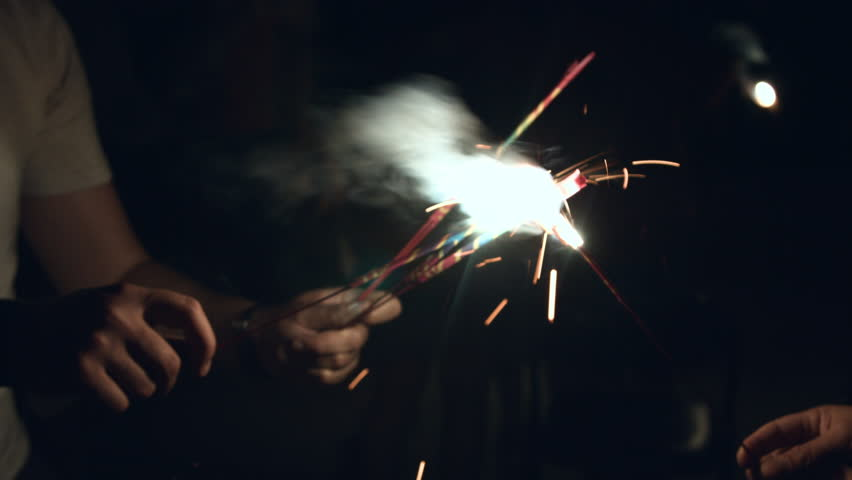 People holding three firework sparklers on a summer night during the 4th of july
