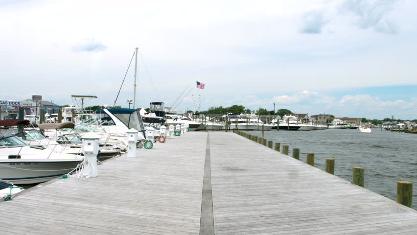 Girl walking down pier near the ocean and boats in Long Island New York