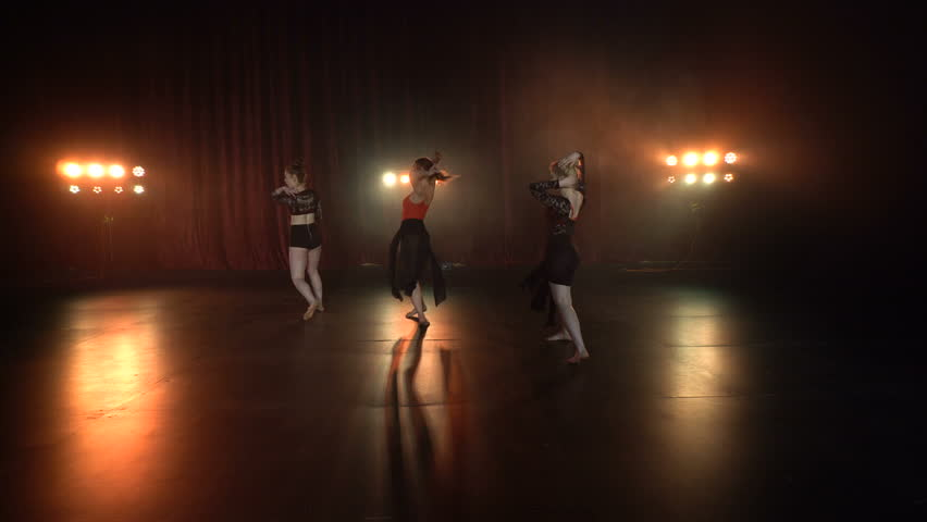 Dance performance of sexy female group on a dark stage with orange lights and smoke  | Shutterstock HD Video #18345658