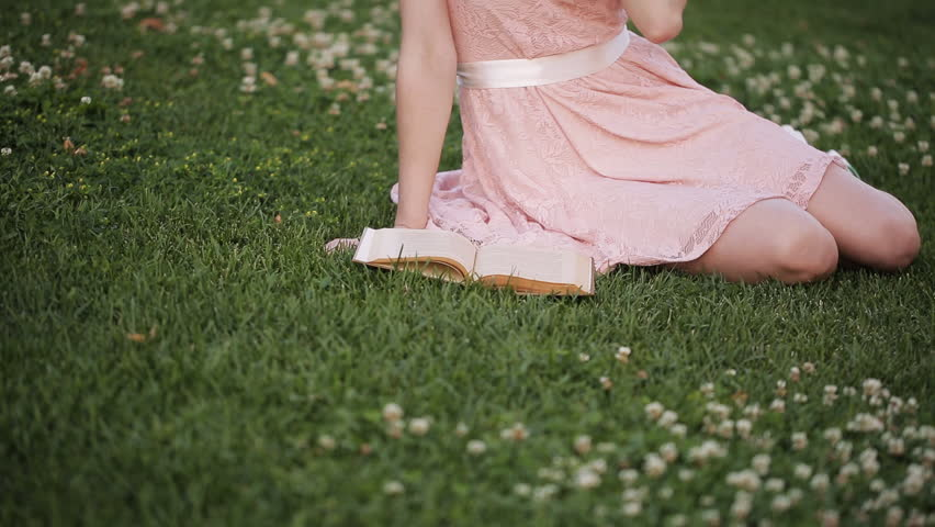 The girl on the lawn in the park reading a book and dreaming about love | Shutterstock HD Video #18390514