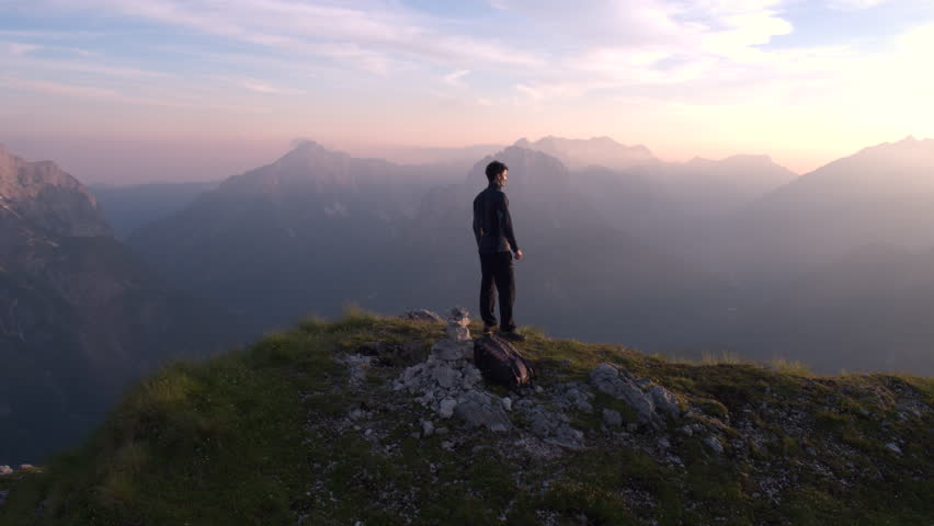 Aerial - Flying from front to behind the man standing on top of the mountain watching beautiful sunset over the peaks | Shutterstock HD Video #18395320
